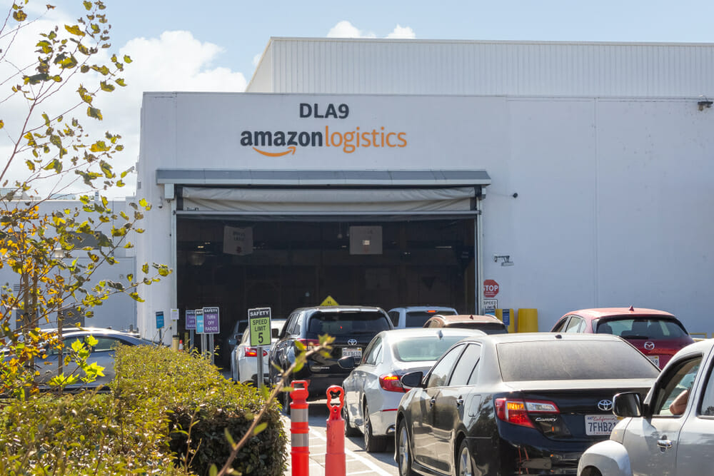 Amazon Flex drivers queue in front of a fulfilment centre in their own cars.